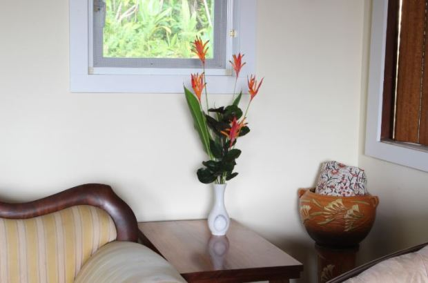 This arrangement has a good height ratio of vase to plants. The rule is that the vase should (generally) be about one third the height of the full arrangement, including the vase. The arrangement also has good relationship energy because there's more than one flower (parakeet heliconia). There's a good yin/yang balance because some of the plants have an bright, upward energy which is balanced by the darker, rounded-leaf foliage of dinnerplate panax. Note that even though some of the plants are pointy, they don't point at people.