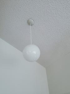 plain white globe pendant light hanging from the ceiling